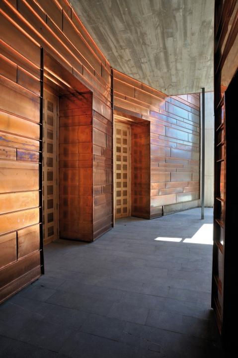 Korytarz prowadzący do atrium krematorium w Saragossie. Miedziane panele i beton.