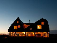 Dom wydmowy w Thorpeness: przeszklony parter i zapewniające prywatność pomieszczenia na piętrze. Mies van der Rohe Award 2013